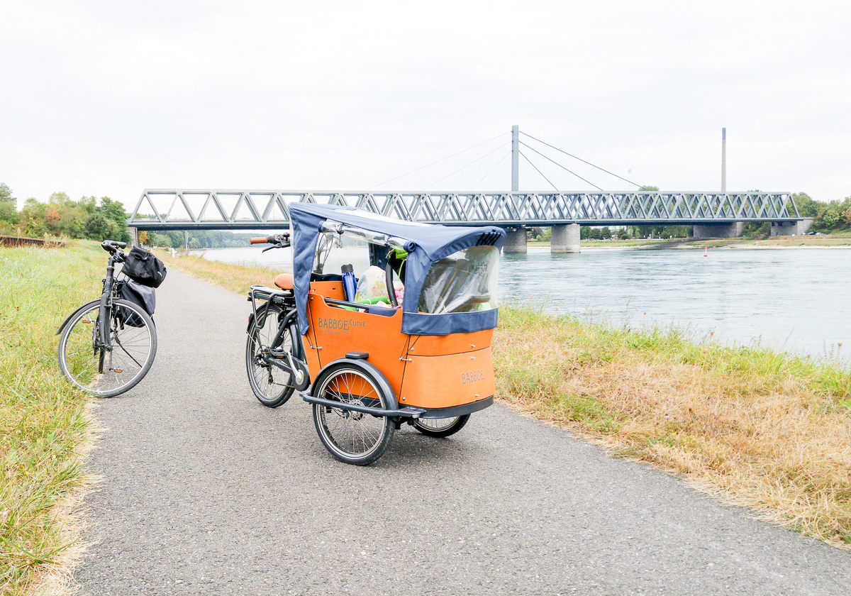 Brücke über dem Rhein Babboe Lastenrad Curve-E Elektro Lastenfahrrad für Fahrradurlaub und Fahrradtour mit Baby und Kind vorne drin