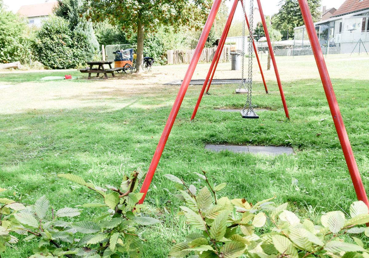 Pause machen während der Radtour mit Baby und dem Babboe Curve-E Lastenfahrrad auf dem Spielplatz an der roten Schaukel