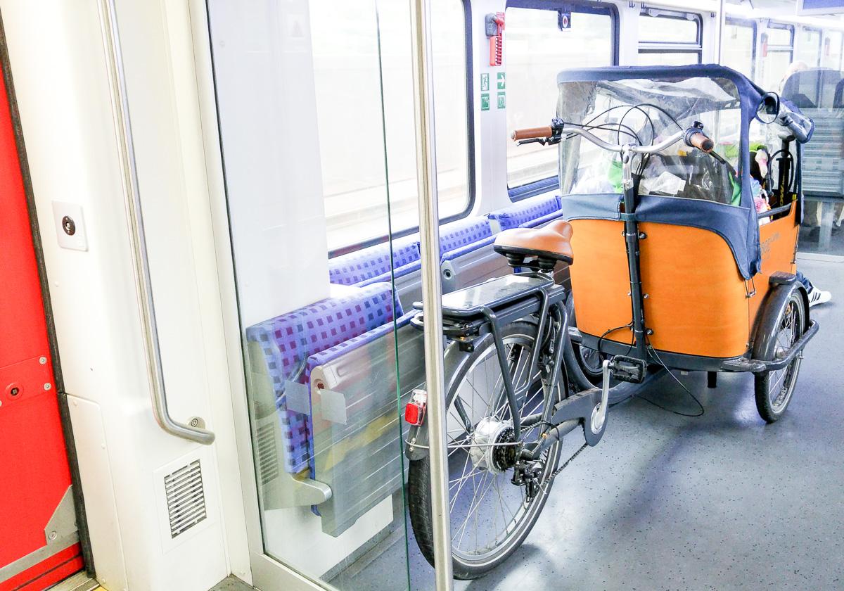 Zug fahren mit dem Babboe Lastenrad Curve-E nach der Fahrradtour am Rhein von Karlsruhe nach Straßburg mit Baby und Kind im Lastenfahrrad vorne